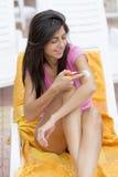 应用太阳保护奶油的美丽的微笑的妇女 免版税库存图片