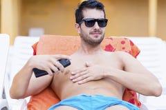 应用太阳保护奶油的英俊的微笑的人 免版税库存照片