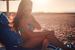 应用太阳奶油的女孩,当坐海滩时 免版税库存照片