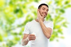 应用奶油或化妆水的愉快的年轻人于面孔 免版税库存图片