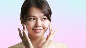 应用奶油的年轻中国妇女于面孔 股票录像