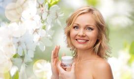 应用奶油的愉快的妇女于她的面孔 库存图片