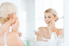 应用奶油的愉快的妇女于面孔在卫生间 免版税库存图片