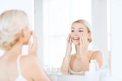 应用奶油的愉快的妇女于面孔在卫生间 库存图片
