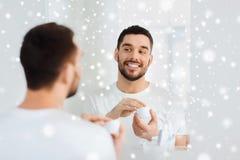 应用奶油的愉快的年轻人于面孔在卫生间 库存图片