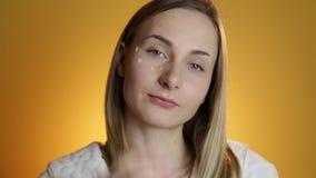 应用奶油的美丽的妇女特写镜头画象于面孔skincare概念 影视素材