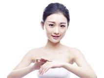 应用奶油的年轻亚裔妇女 免版税库存图片
