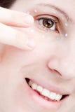 应用奶油色眼睛皮肤妇女 免版税库存照片