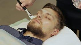 应用奶油面具 按摩面孔和脖子 有胡子的人 透明质酸面具 影视素材