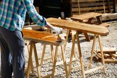 应用新鲜的木治疗油漆的工作者 免版税库存图片