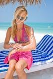 应用晒黑化妆水的妇女在一个热带海滩 库存图片