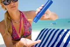 应用晒黑化妆水的妇女 免版税库存照片
