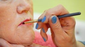 应用有刷子的化妆师唇膏在嘴唇成熟妇女关闭 股票录像