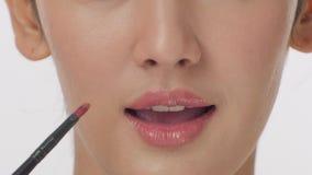 应用有刷子的化妆师液体唇膏在嘴唇少妇 影视素材