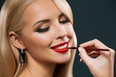 应用有构成刷子的可爱的微笑的妇女红色唇膏, 免版税库存照片