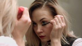 应用染睫毛油和敬佩的秀丽十几岁的女孩在镜子 库存照片