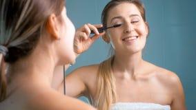 应用染睫毛油的美丽的微笑的妇女画象在卫生间 免版税库存图片