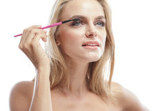 应用染睫毛油的美丽的白肤金发的妇女 免版税库存图片