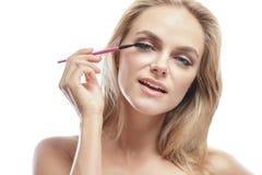 应用染睫毛油的美丽的年轻白肤金发的妇女 库存图片