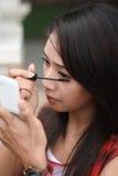应用染睫毛油纵向俏丽的妇女年轻人 免版税库存照片