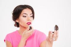 应用桃红色唇膏和看镜子的可爱的少妇 免版税库存照片
