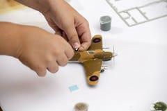 应用水滑道标签的男孩手于塑料模型 免版税库存照片