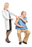 应用注射器的女性医生于一个年长人 库存照片