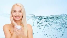 应用润湿的奶油的妇女于她的面孔皮肤 图库摄影