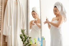 应用润肤膏的少妇在镜子附近 免版税库存照片