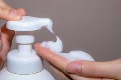 应用液体皂的女性手 免版税库存图片