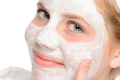 应用清洗的面部面具的年轻微笑的女孩 库存照片