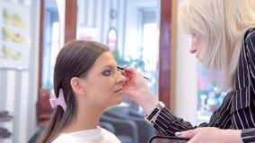 应用眉笔的化妆师于模型的构成 股票录像