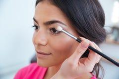 应用眼影膏的化妆师于可爱的妇女 库存图片