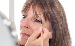 应用眼影膏粉末的妇女 免版税库存图片