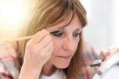 应用眼影膏粉末,光线影响的妇女 免版税库存图片