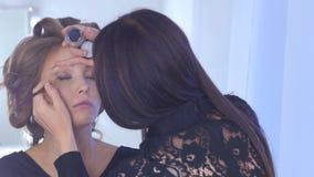 应用眼线膏的专业化妆师在模型的整个眼睛附近 库存图片