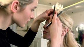 应用眼线膏的专业化妆师在眼睛附近于美容院的白肤金发的妇女 秀丽、构成和时尚概念 股票视频