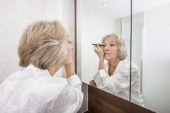应用眼线膏的资深妇女,当看镜子在卫生间里时 免版税库存图片