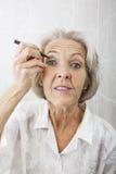 应用眼线膏的资深妇女画象在卫生间里 免版税库存照片