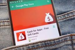 应用程序的现金-赠品在谷歌戏剧在智能手机显示的商店网站上的卡片应用程序掩藏在牛仔裤口袋 免版税图库摄影