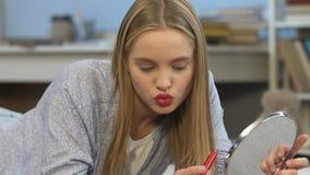 应用红色唇膏的逗人喜爱的十几岁的女孩,感到俏丽和自信 股票录像