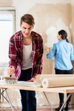 应用胶粘剂的年轻人贴墙纸,当女朋友测量墙壁时 免版税图库摄影