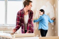 应用胶粘剂的年轻人贴墙纸,当女朋友测量墙壁时 库存照片