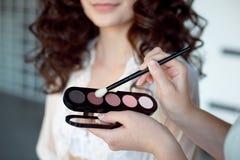 应用艺术家眼睛构成影子 完善的光滑的皮肤 适用构成 阴影的应用在式样` s的注视 免版税库存照片