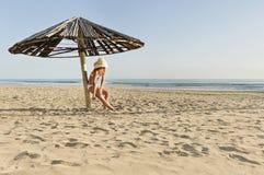 应用遮光剂化妆水的年轻美丽的女孩在伞下在海滩 免版税库存图片