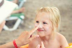 应用遮光剂在逗人喜爱的小的女儿面孔的母亲保护奶油 使用sunblocking的化妆水的妈妈保护孩子女孩免受太阳 免版税库存图片