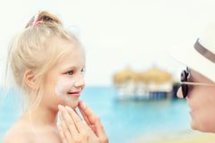 应用遮光剂在逗人喜爱的小的小孩男孩面孔的母亲保护奶油 使用sunblocking的化妆水的妈妈保护婴孩免受太阳 库存图片