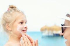 应用遮光剂在逗人喜爱的小的小孩男孩面孔的母亲保护奶油 使用sunblocking的化妆水的妈妈保护婴孩免受太阳 免版税库存图片