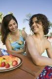 应用遮光剂的妇女于儿子(13-15)在游泳池。 库存照片