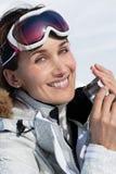 应用遮光剂的滑雪倾斜的妇女 库存图片